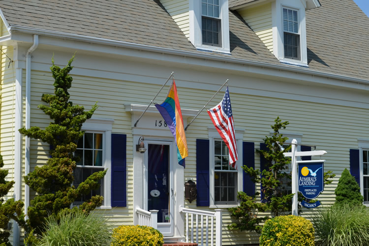 Front of the Inn done in pale yellow with an american flag and rainbow flag flying on each side of the door