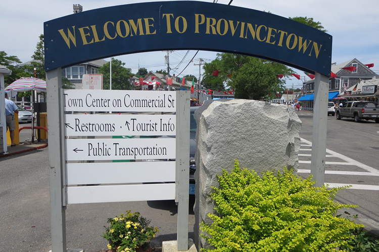 Welcome to Provincetown sign with blue background and gold text, white signs below with directions.