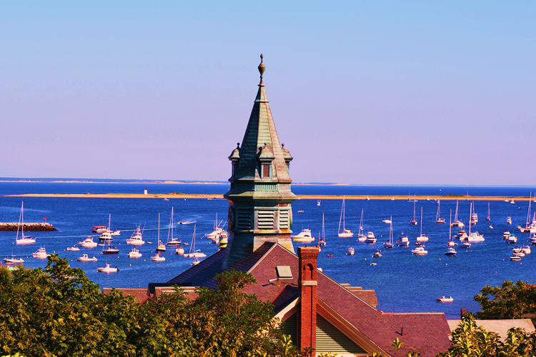 Church steeple with very vibrant blue water and boats in the back ground