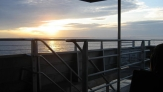 Looking at the yellow sunset thru the railing of the ferry