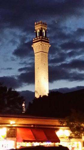 A view of the Pilgrim Monument at night with uplighting on the sides with a dark and mystic clouds behind