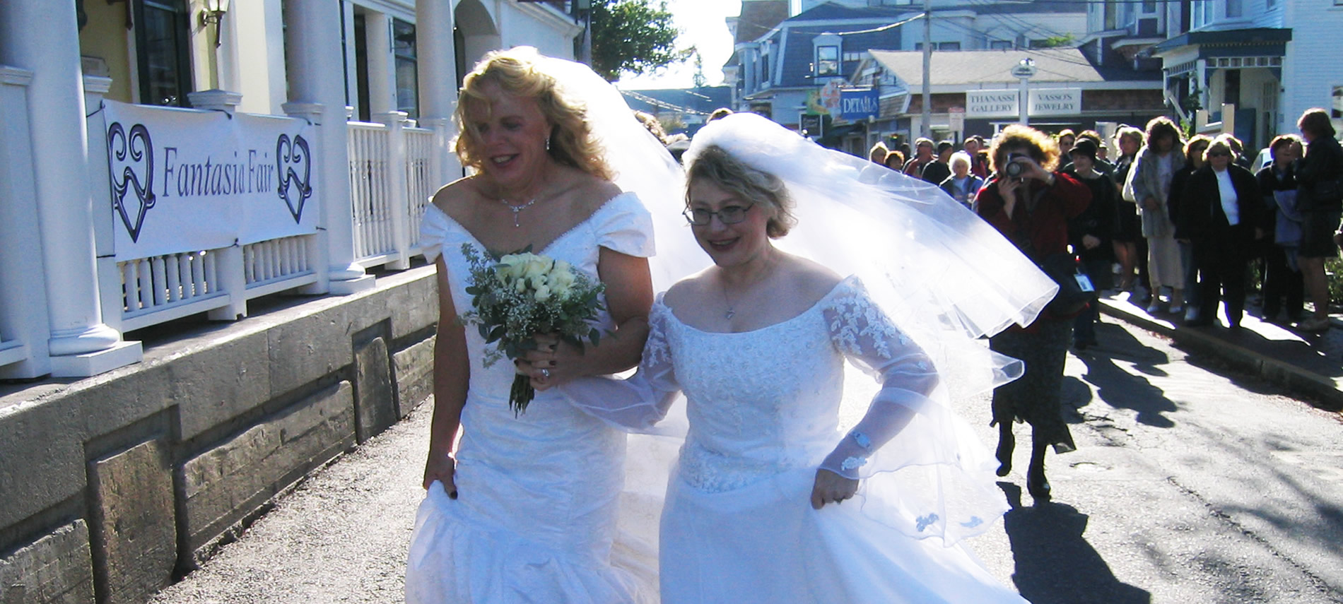 Robyn and Audri In White Wedding gowns walking down the main street with people lining the street