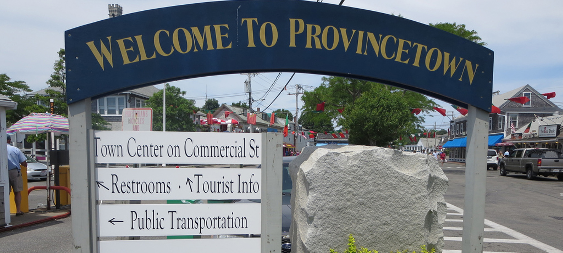 Blue with gold Sign  says Welcome to Provincetown With directional signs below done in black text and white background