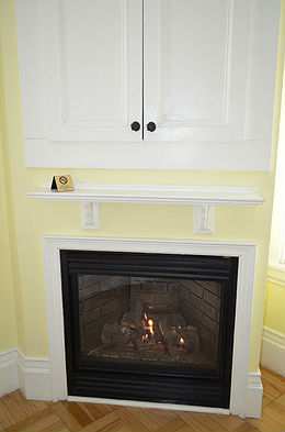 Built in white cabinet and gas fireplace into a yellow corner wall