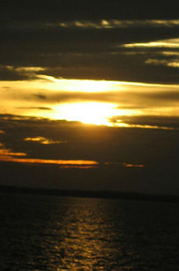 beauiful sunset behind the clouds creating Yellow and black in the sky with very dark water