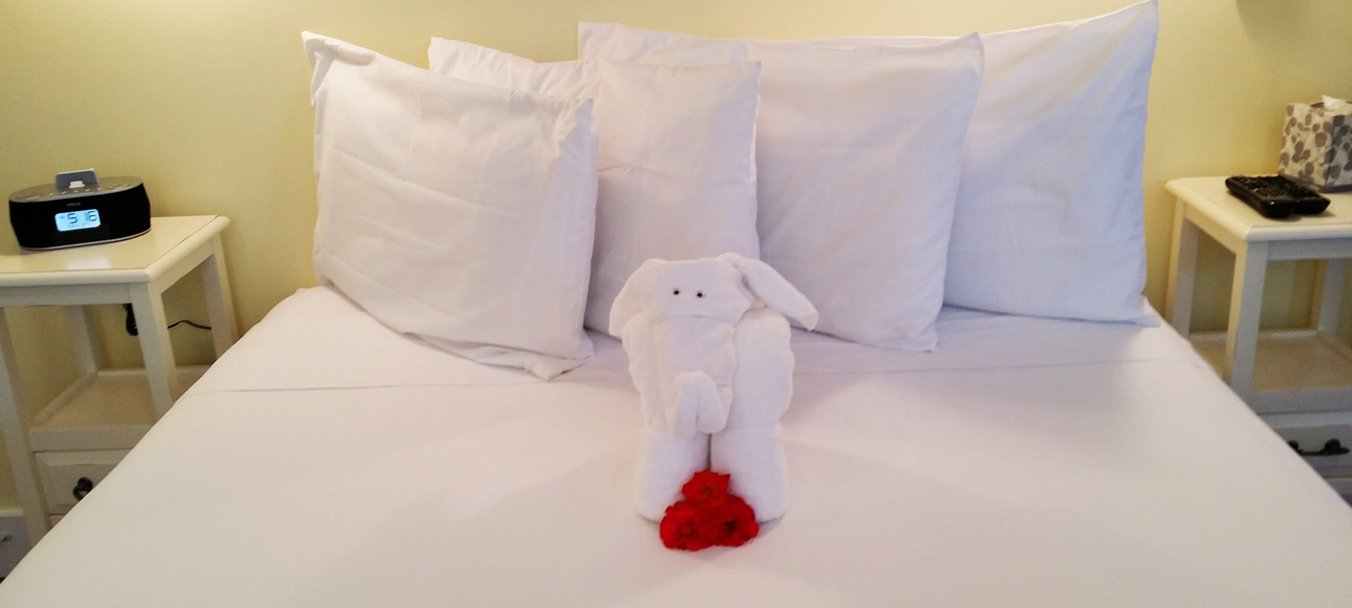 Towel sculpture of an elephant sitting on the bed with flowers by its feet