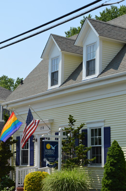 The Front of the Inn done in Yellow and navy blue shutters, American and Rainbow flags flying on each side of the front door