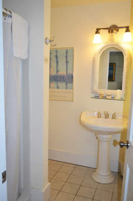 Room 1 has a private bathroom with a shower and a pedestal sink