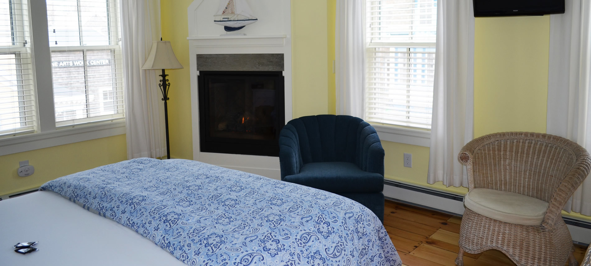 Room 3 Second floor, queen bed with a white bedspread, with blue/white paisley comforter at the bottom of bed, One navy blue chair and one tan wicker chair, Fireplace lite. Yellow walls and white curtains