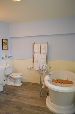 air-jetted pedestal tub, white fluffy towels on a warming rack, white toilet. Blue walls on top and yellow wyane coat on bottom.