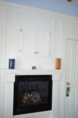 RM 6 a wall of white woodwork with a built in cabinet and gas fireplace