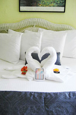 Two Swans made from the white towels kissing each other with a flower on each side sitting on a bed with white sheets and a blue comforter