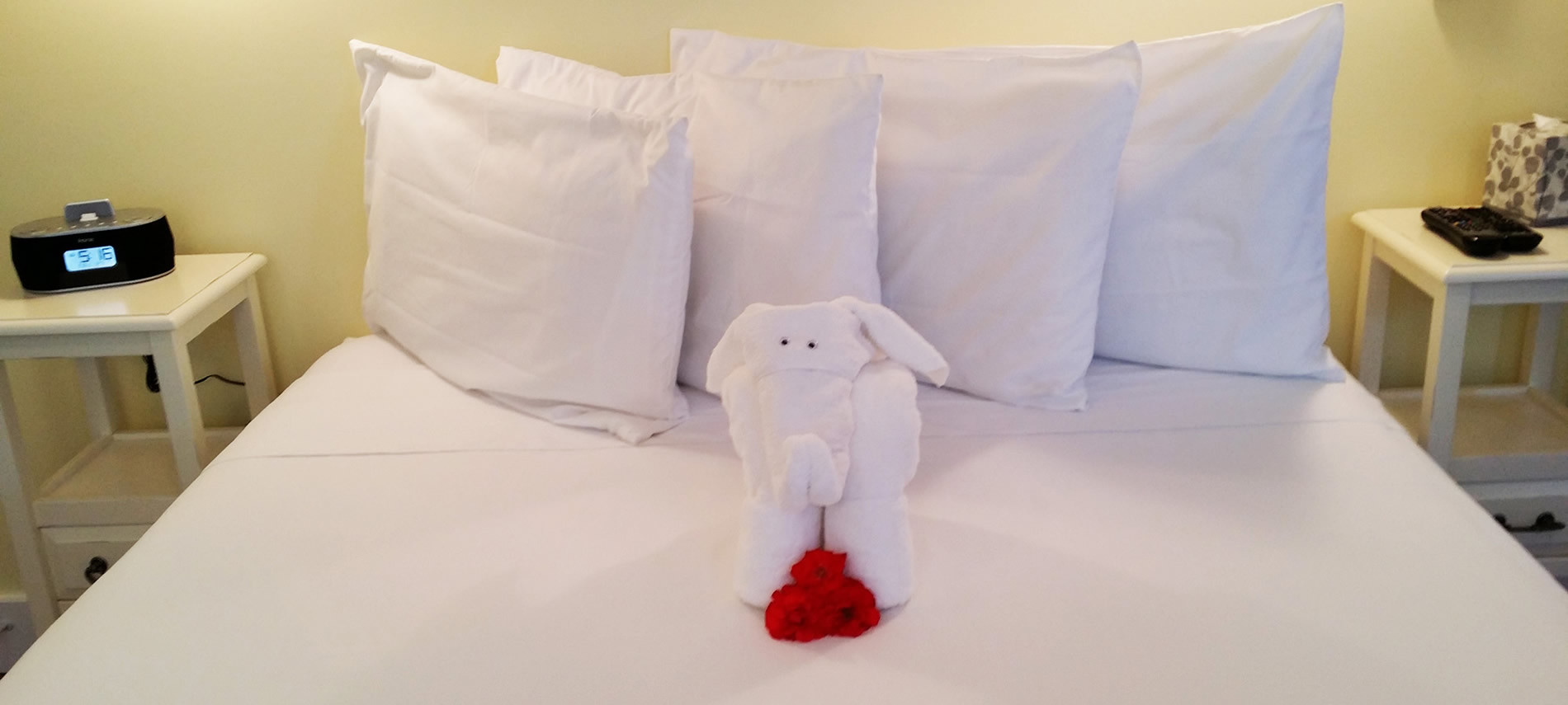 Towel sculpture of an elephant sitting on the bed with flowers by its feet. White bedspread and two nightstands
