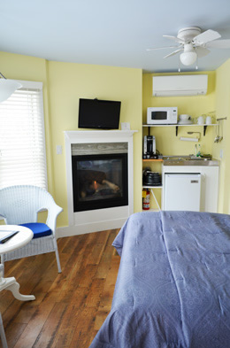 Gas fireplace built into the corner Yellow wall, tv mounted above. Kitchenette with Microwave, mini frig, and sink. Hardwood floors