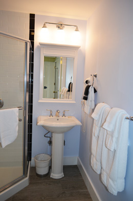 Studio Forward has a private bathroom with a glass enclosed corner shower and heated floors
